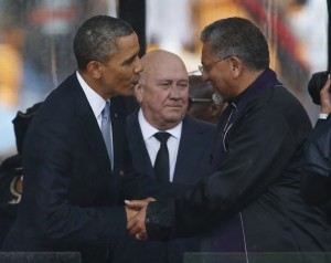 Obama and de Klerk greet Methodist Bishop Ivan Abrahams at Mandela's Memorial today.