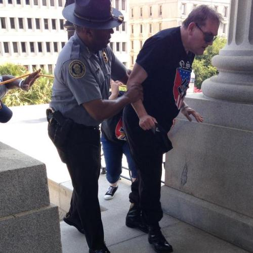 Police officer Leroy Smith helps an overheated man wearing National Socialist Movement attire up the stairs during a KKK rally & counter protest on July 18, 2015, in Columbia, S.C.  Temperatures that day reached in the upper 90s.